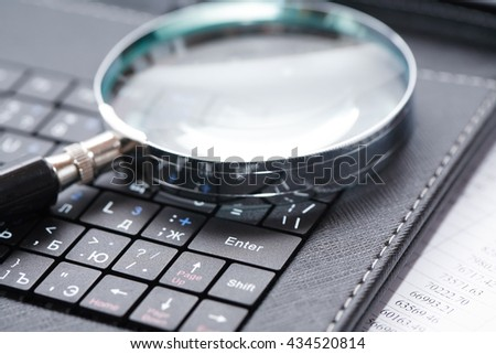 Business concept. Magnifying glass on black laptop keyboard - stock photo