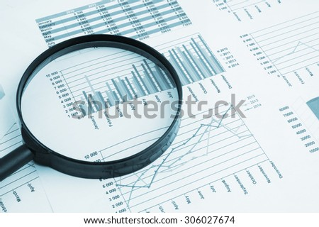 Business concept, magnifying glass on financial charts and graphs - stock photo