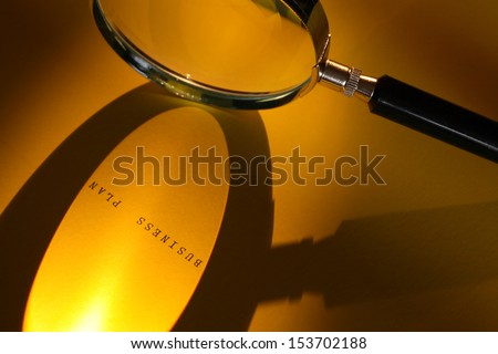 Business concept. Magnifying glass on paper surface with BUSINESS PLAN inscription - stock photo