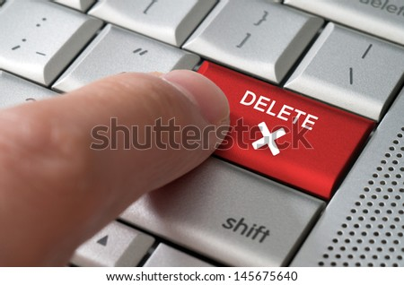 Business concept male finger pointing delete key on  a metallic keyboard - stock photo
