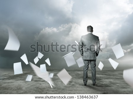 Business concept - Paperwork flying around a businessman.