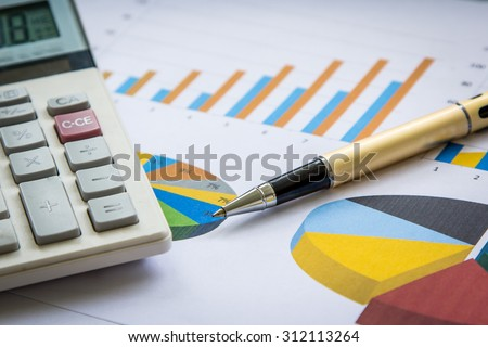 Business concept, Pen and calculator on graph background - stock photo