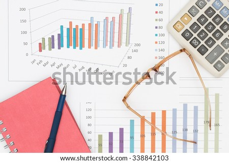 Business concept : Pen placed on notebook with glasses and calculator on graph background.