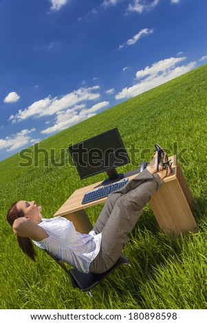 Business concept shot of a beautiful young woman businesswoman relaxing at an office desk & computer in a green field with a bright blue sky & white clouds.