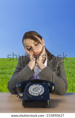 Business concept shot of a beautiful young woman businesswoman sitting at a desk waiting for old vintage telephone to call in  green field with a bright blue sky.