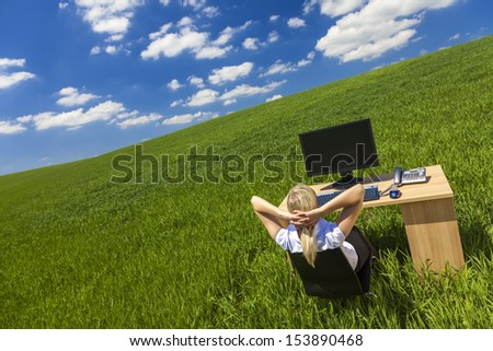 Business concept shot of a beautiful young woman or businesswoman relaxing at a desk with computer in a green field with a bright blue sky.  - stock photo