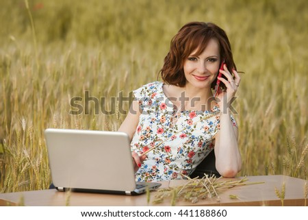 Business concept shot of a beautiful young woman sitting at a desk using a computer in a field. Young businesswoman in sunny meadow nature office.  Young woman with laptop outside.
