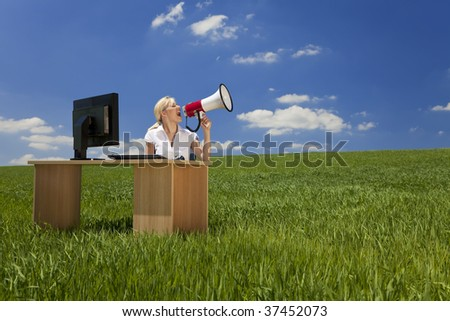 Business concept shot of a beautiful young woman sitting at a desk using a megaphone in a green field with a bright blue sky. Shot on location. - stock photo