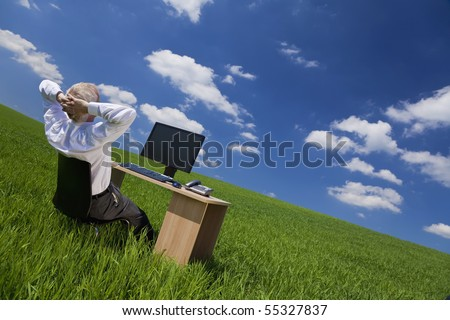 Business concept shot of a middle aged man or businessman relaxing with hands behind his head at an office desk with computer in a green field with a bright blue sky. Shot on location.