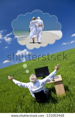 Business concept shot of a senior male executive businessman sitting at work desk in field, arms raised dreaming of tropical romantic beach vacation holiday or retirement with his wife or girlfriend - stock photo