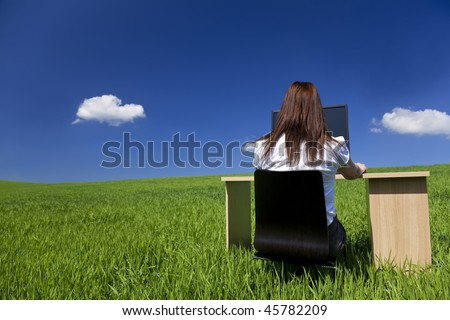 Business concept shot of a young woman working at an office desk and computer in a green field with a bright blue sky and fluffy white clouds. Shot on location.