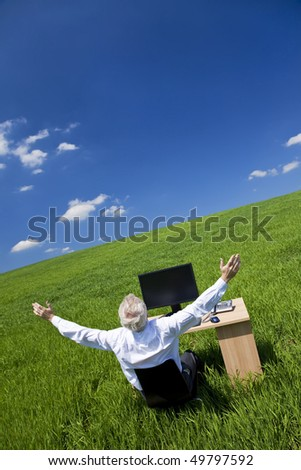 Business concept shot showing an older male executive arms raised using a computer in a green field with a blue sky complete with fluffy white clouds. Shot on location not in a studio. - stock photo