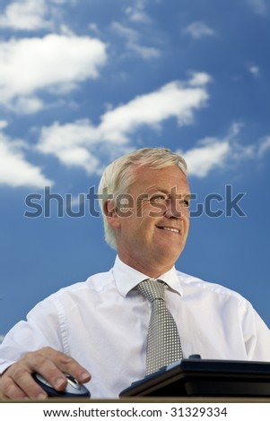Business concept shot showing an older male executive using a computer with a blue sky complete with fluffy white clouds. Shot on location not in a studio. - stock photo