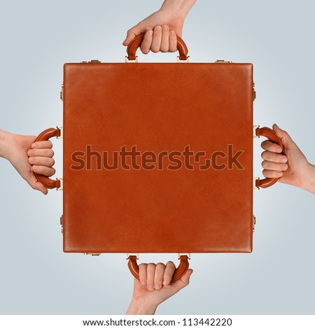 business concept showing multiple hands holding a briefcase - stock photo