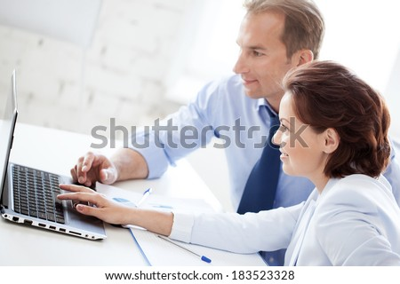 business concept - smiling businesswoman and businessman working with laptop in office - stock photo