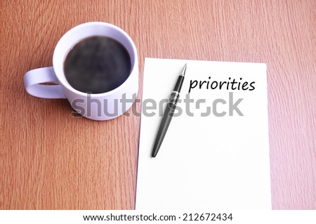 Business Concept - Steamy Coffee And Black Pen With White Paper Writing Priorities On The Table  - stock photo