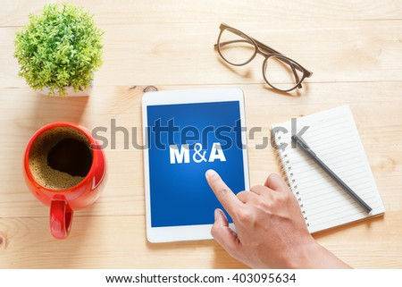 """Business concept.Tablet with text inside """"M&A (Merger and Acquisition)"""" on the table with offee. - stock photo"""