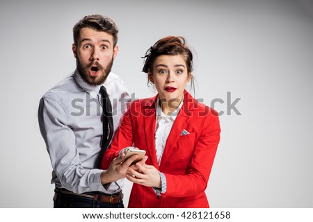 Business concept. The two surprised young colleagues holding mobile phone and speakikng on gray background - stock photo