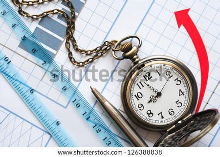 Business concept. Watch and ruler on paper background with red chart - stock photo
