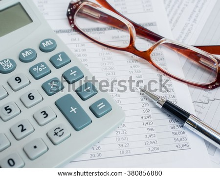 Business concept with calculator,pen,glasses and financial documents.