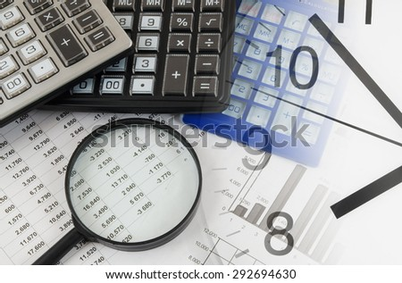 Business concept with clock, magnifying glass, calculators and documents - stock photo