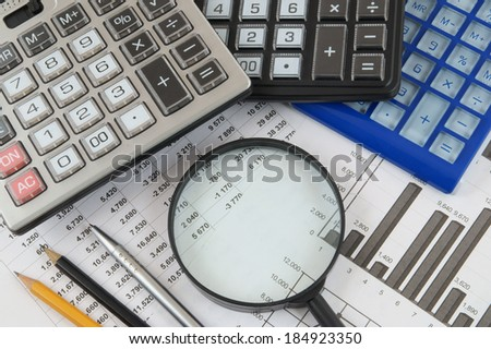 Business concept with magnifying glass, calculators and documents  - stock photo