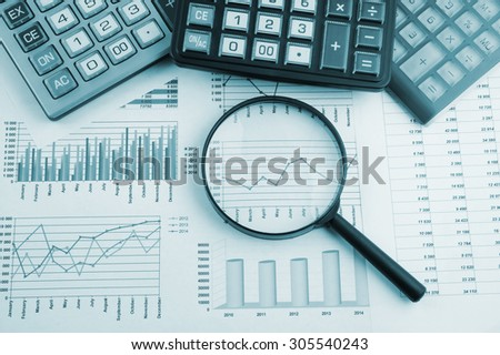 Business concept with magnifying glass, calculators and documents