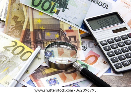 Business concept with money Euro and calculator on wooden board