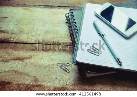 Business concept with paper agenda pen and smartphone on the wood table - stock photo