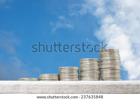 Business concept with stacks of coins against blue sky background - stock photo