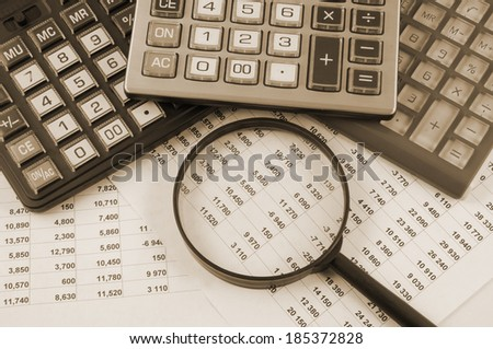 Business concept with three calculators and magnifying glass on documents