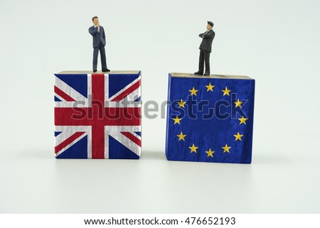 business concept with UK flag and EU flag on wood block and mini businessman - isolate on white background