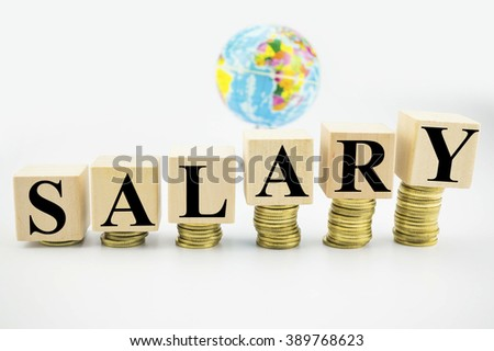 Business Concept: Wooden block with stacked coins with word Salary written
