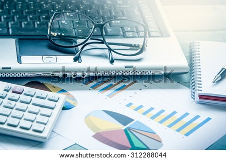 Business concept,working,analyzing,glasses on laptop with calculator on graph background in blue filter effect - stock photo