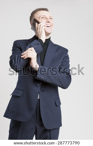 Business Concept: Young Caucasian Businessman in Blue Suit Speaking Using Cellphone. Over White Background.Vertical Image