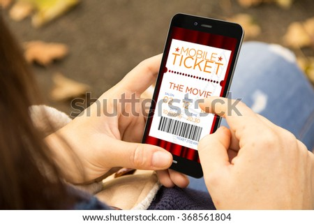 business concept: young woman with online cinema tickets phone at the park. All screen graphics are made up. - stock photo
