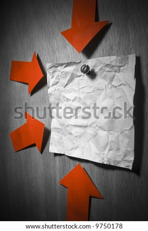Business conceptual image. Crumpled office note paper attached to wall by screw and pointed by red arrows - stock photo