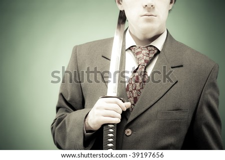 Business conceptual image: young businessman standing with sword. Hard business, busines is a struggle concept - stock photo