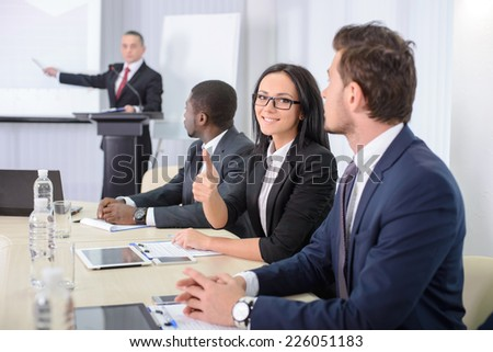Business conference. Business meeting. Business people in formalwear discussing something while sitting together at the table