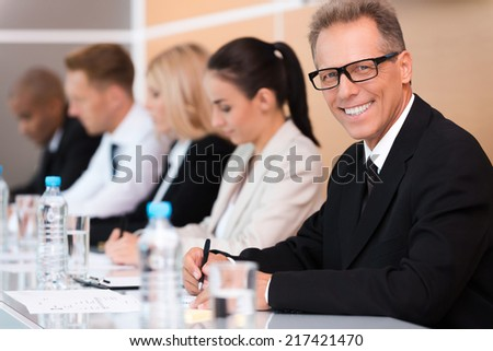 Business conference. Group of business people sitting in a row and writing something in their note pads while confident mature man in formalwear looking at camera and smiling  - stock photo