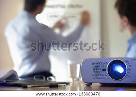 Business conference or lecture with businessman writing on whiteboard and lcd projector in foreground - stock photo