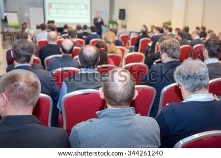 business conference: rear view of the people in a conference hall - stock photo