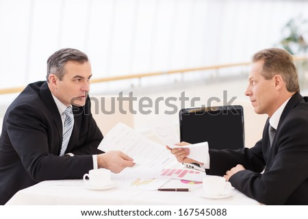 Business confrontation. Two mature men in formalwear arguing while sitting together at the table - stock photo