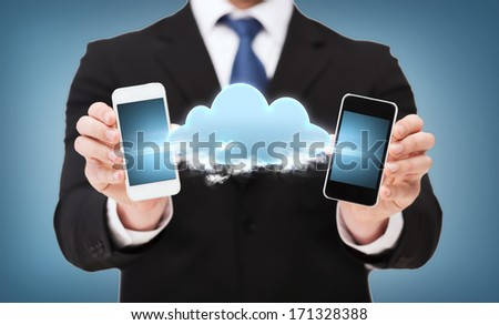 business, connectivity,internet and technology concept - businessman showing two smartphones black connected with cloud - stock photo