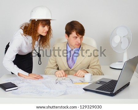 Business construction industry team with engineering drawing looking on laptop in white office