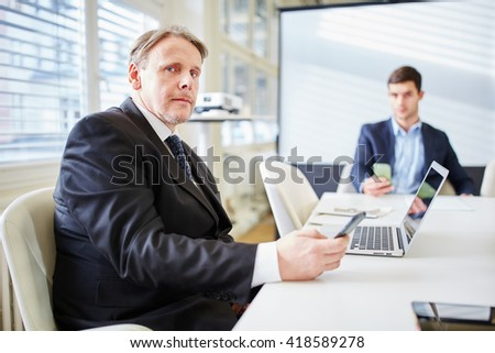 Business consulting man in business meeting with smartphone and computer