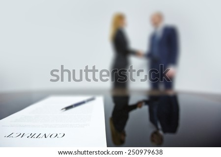 Business contract with pen on background of co-workers handshaking - stock photo
