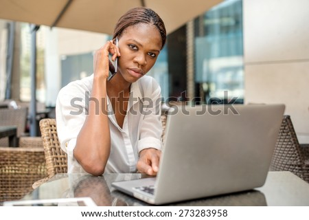 Business conversation with a client in Dubai. African businesswoman businessman holding a cell phone and talking to a customer at a cafe table in Dubai downtown with a laptop - stock photo