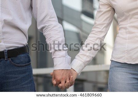 Business couple holding hands
