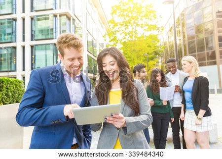 Business couple looking at digital tablet. On background there are some more persons. They all are young, smiling and wearing smart casual clothes. Mixed race group. Teamwork and business concepts. - stock photo